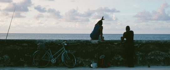 Two people on a beach wall
