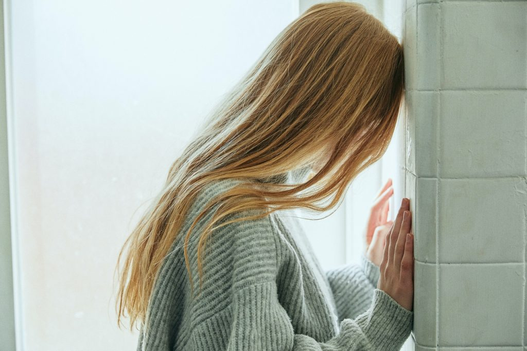woman leaning her head against a wall