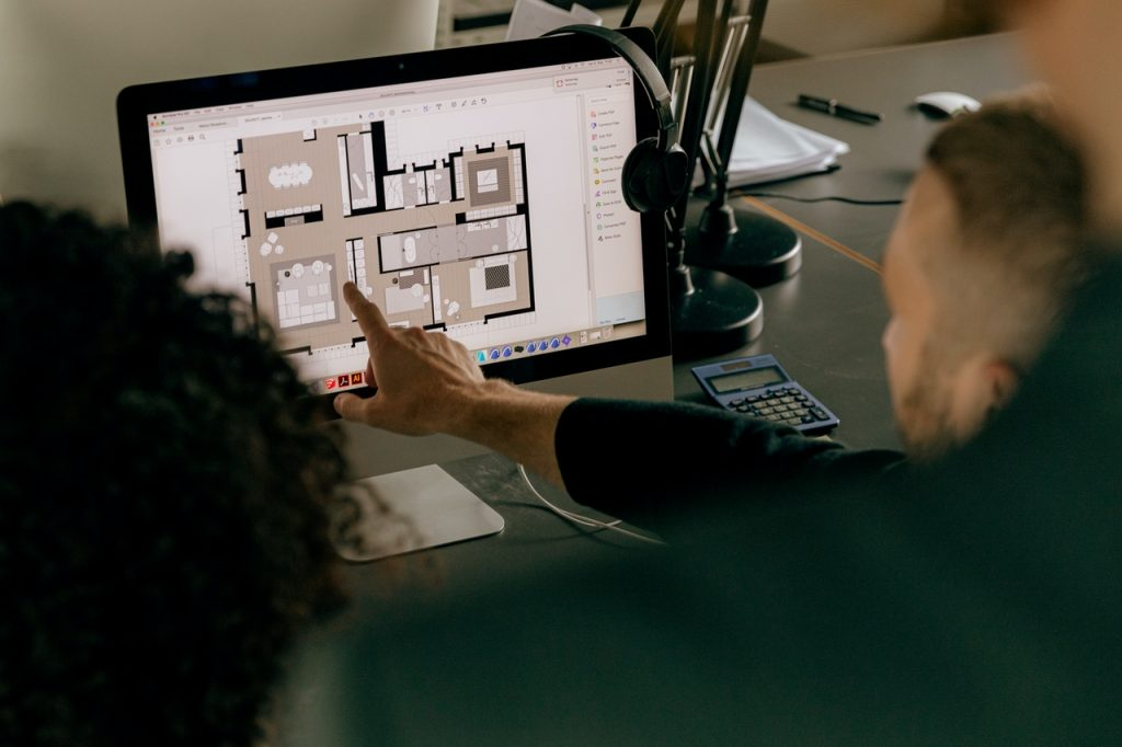 person pointing at an architectural design on a computer screen