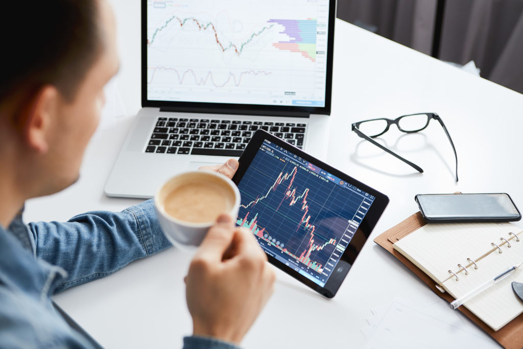 Person looking at a stock portfolio while drinking coffee