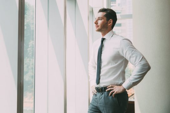 man in business attire looking out a window